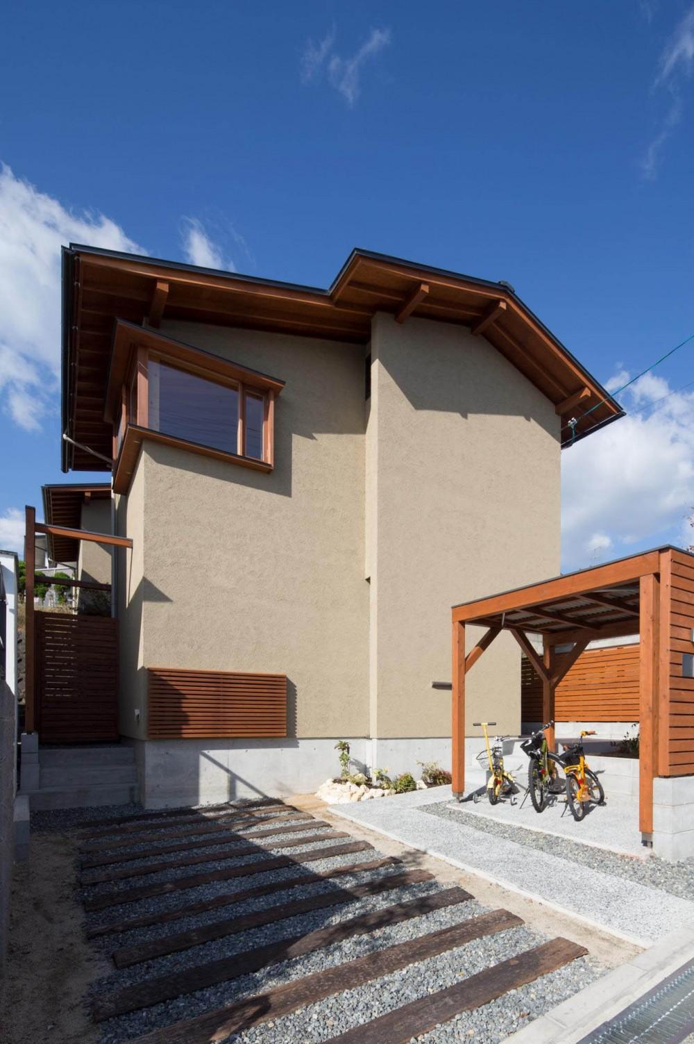 日吉台の家/大きな屋根の下にスキップフロアで各部屋が繋がる大らかな住まい (外観/目隠しを兼ねた屋根付き駐輪場の横を通って玄関へアプローチ)