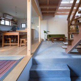 日吉台の家/大きな屋根の下にスキップフロアで各部屋が繋がる大らかな住まい (廊下から居間を見る/玄関から居間までモルタルの土間が続きます)
