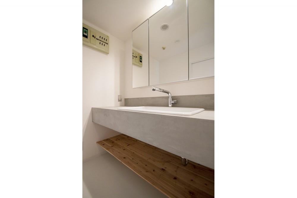 グレーホワイトな空間に、ネイビーの対面キッチンが空間の主役 (サニタリー)