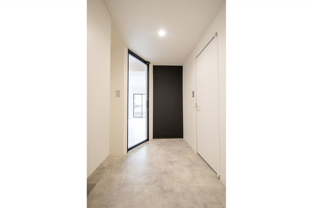 グレーホワイトな空間に、ネイビーの対面キッチンが空間の主役 (玄関)