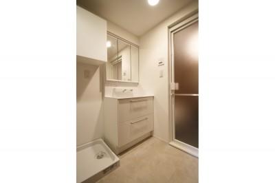 サニタリー (ヘリンボーンの床に、キッチンは塗装仕上げの木製モールディング)