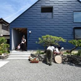 藍いろの家~横葺きのガルバリウム外壁が特徴の家型のおうち。家型フォルムの中の通り土間は家族のお気に入り~ (外観~メダカをのぞき込む父と息子たち)