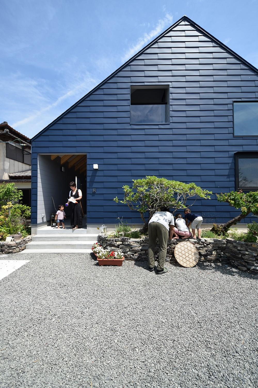 外観~メダカをのぞき込む父と息子たち (藍いろの家~横葺きのガルバリウム外壁が特徴の家型のおうち。家型フォルムの中の通り土間は家族のお気に入り~)