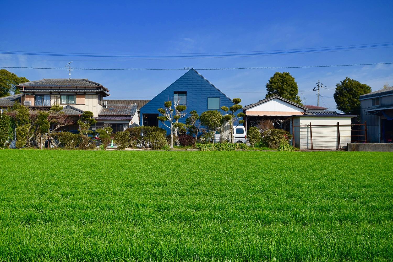 外観事例:田園風景の中の藍いろの家~四季を通じて風景に馴染む(藍いろの家~横葺きのガルバリウム外壁が特徴の家型のおうち。家型フォルムの中の通り土間は家族のお気に入り~)