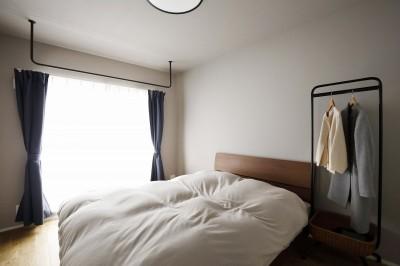 洗練されたショップのような主寝室 (赤と躯体が映える家)