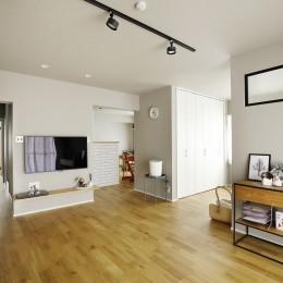 ダイニング・キッチンとリビングは躯体壁で空間分け (赤と躯体が映える家)