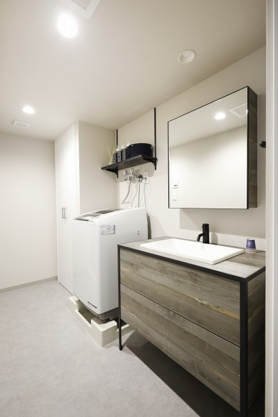 モノトーンでも温かみのある洗面スペース (赤と躯体が映える家)
