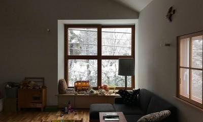 雪の日のリビング|木々と木の窓の家
