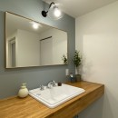ヘリンボーンのフローリングが映えるアンティークリノベの写真 洗面室