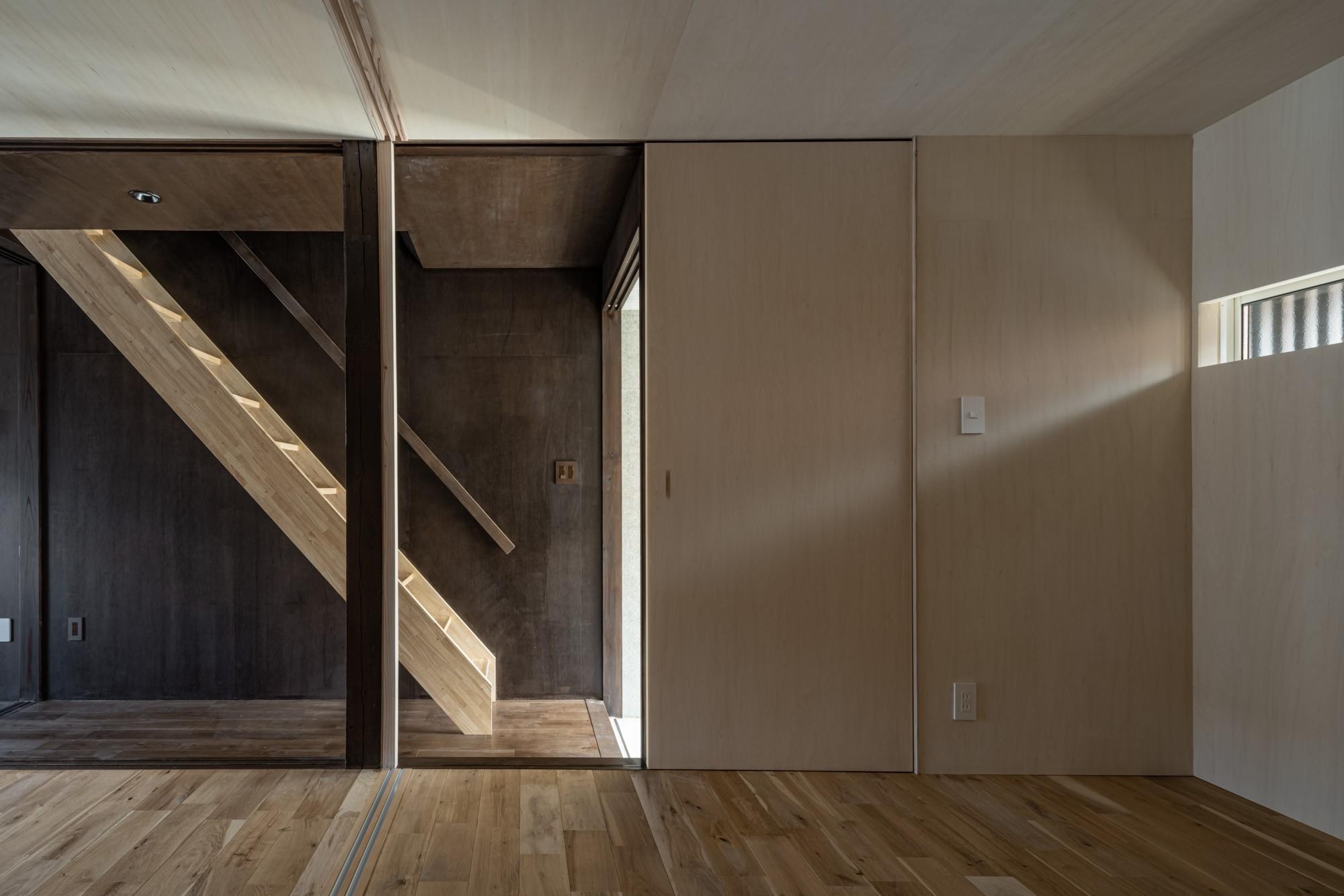 その他事例:玄関横の部屋から階段をみる /光を抑制した空間はシナ合板で明るく設えている。(『RE長屋‐ITO2』~新:旧・モダン:和 のコラボ~(古民家再生))