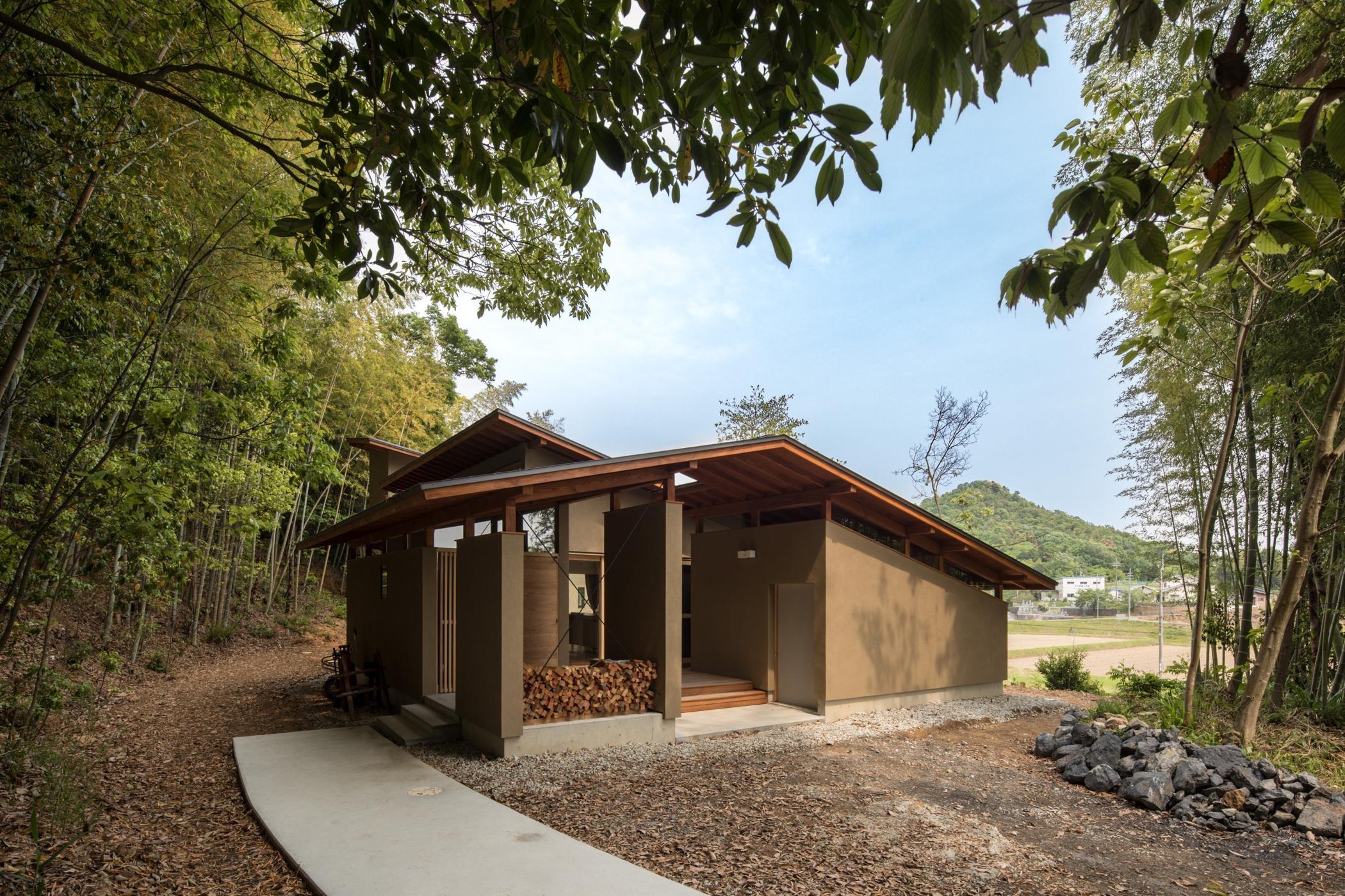 外観事例:薪置き場が特徴的な玄関ポーチ。(竹林の家/里山と竹林に囲まれながら田園風景を見渡す大らかな住まい)