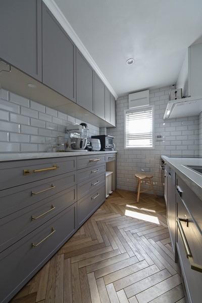 ヘリンボーンの似合う上品で少しカジュアルな住まい (グレイ扉にサブウェイタイル、真鍮の取っ手をコーディネート)
