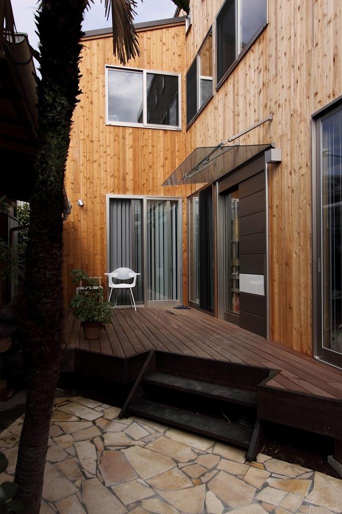 緑豊かな敷地環境を継承する木造スケルトンハウスの部屋 ウッドデッキ~エントランス