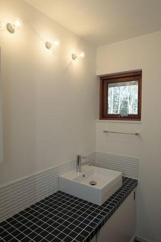 森を眺める黒い家の写真 洗面洗髪室