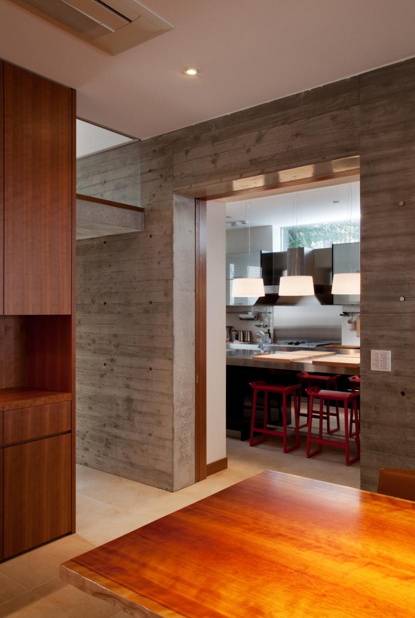「H Residence」緑豊かな庭に囲まれたRC造の邸宅の部屋 食堂よりキッチンを見る