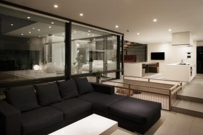 「S Residence」斜面地に建つ開放的な邸宅 (夜景 ファミリーリビングから見通す)