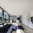 「S Residence」斜面地に建つ開放的な邸宅の写真 ファミリーリビングよりキッチン方向を見る