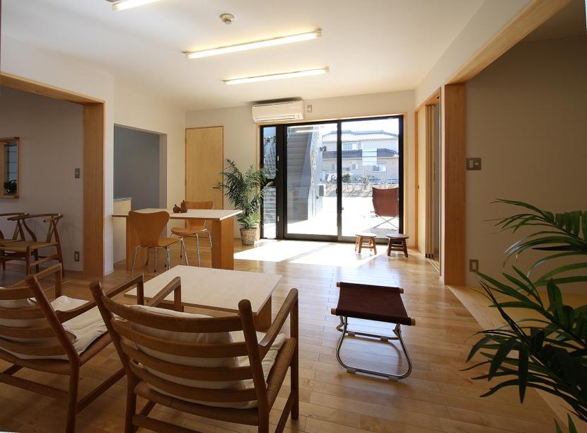 ウッドデッキのある二世帯の家 (バリアフリーで他の部屋と繋がる居間・食堂)