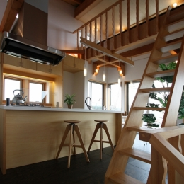 階段より厨房を見る。開放的なアイランドキッチン・居間・食堂。