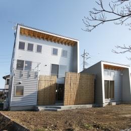 庭を抱える家 (ガルバリウム鋼板の無機質な外観に、ヨシズの柔らかな質感がアクセントになっています。)