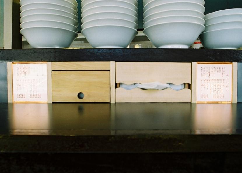 らあめん店の家の部屋 お店のメニューの照明ボックス、ティッシュ入れ、調味料入れをカウンターの下に造り付けました。
