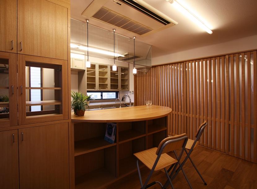 格子ずくしの家の写真 対面キッチンのカウンターを円弧状に大きく取って、夕食も取れるような大きさにしました。