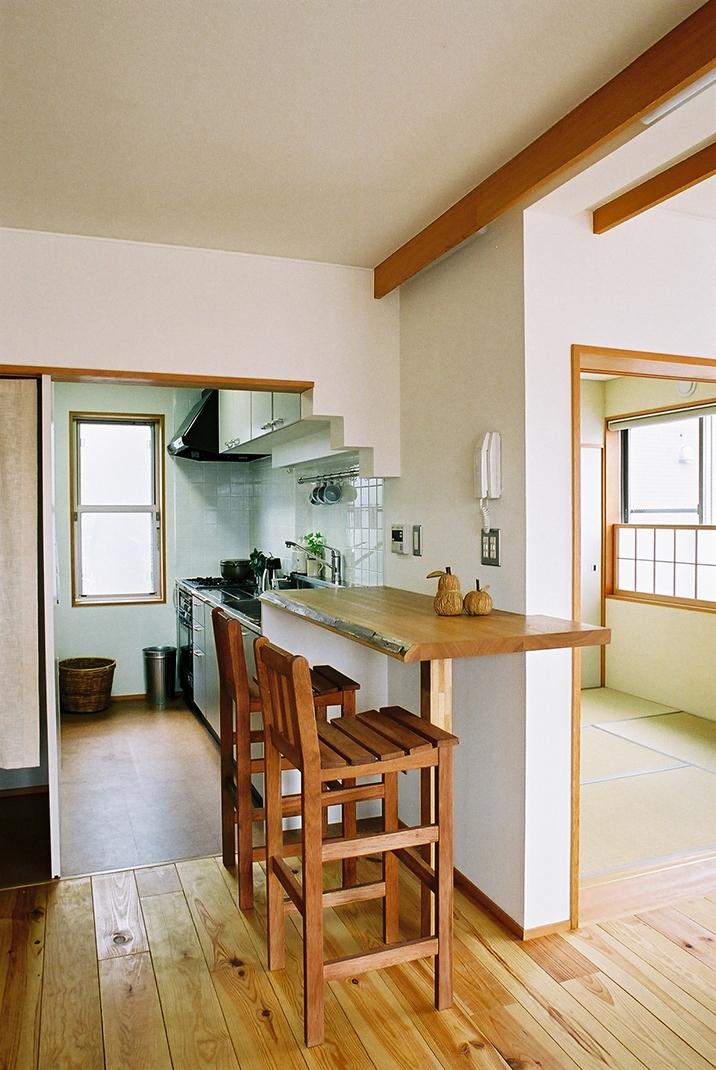 空中テラスのある二世帯の家の部屋 無垢の厚板カウンターがアクセントのキッチン