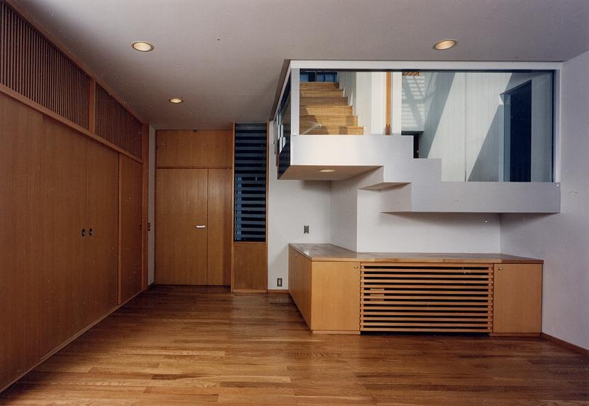 シースルー階段のある家の部屋 全部がガラスの階段室は居間にも降りて来ます。その階段の壁の部分もガラスにすることで、上からの光を取入れるのと同時に、上下に分けた2世帯の気配をそれぞれが感じられるように視覚的に楽めるようにしました。