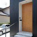 アプローチの床は平板コンクリート。玄関扉は高さ2.6Mのナラ練付。