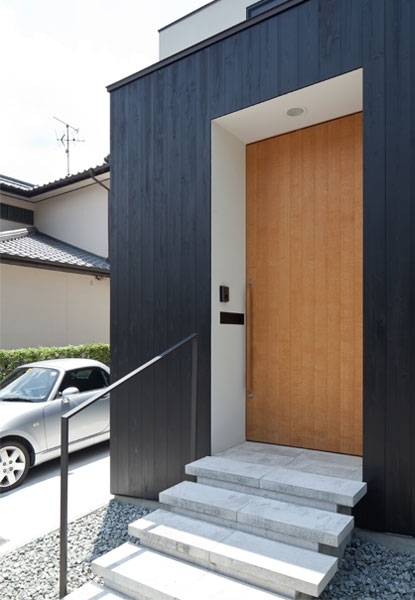 小さな中庭と大きな縁側|プライバシーを守りながら開放的に住む住宅【奈良県生駒市】 (アプローチの床は平板コンクリート。玄関扉は高さ2.6Mのナラ練付。)