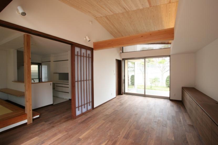 風景が透過する和モダンの家の部屋 畳ダイニングキッチンと繋がるリビング