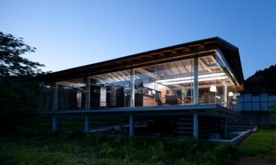 都幾川縁りのハイブリッド・ハウス/Onさんの家 (川辺からの夜の佇まい)