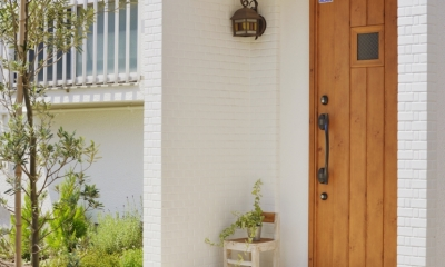 木のドアと白い外壁がまぶしいエントランス。|子供が走り回る家