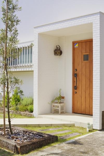 子供が走り回る家 (木のドアと白い外壁がまぶしいエントランス。)