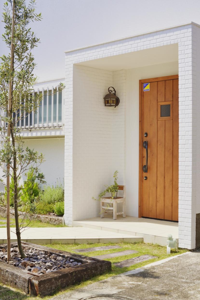 子供が走り回る家の部屋 木のドアと白い外壁がまぶしいエントランス。