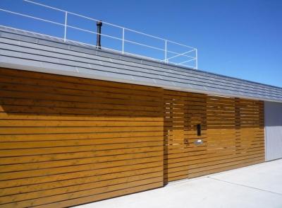 ガレージとソト土間のある家 Beetle House (連続した板塀とガレージドア)