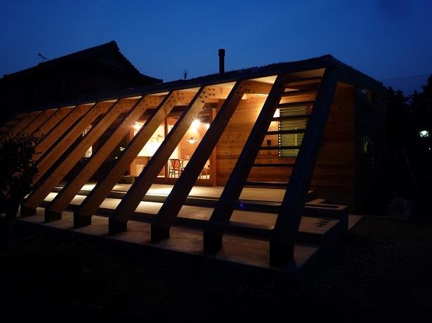 大地に根付く家|mat house (外観夜景|ルーバーのような13本の梁)