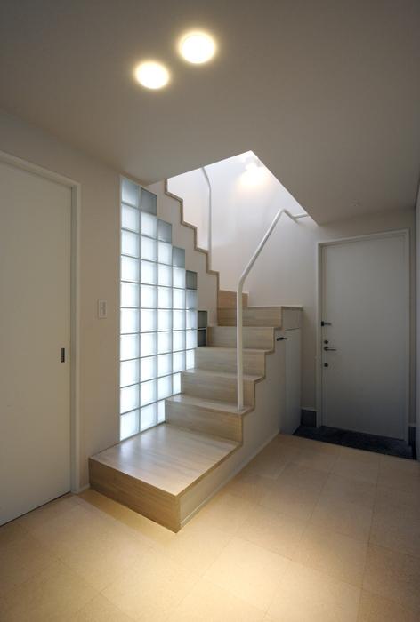 ひかりの架け橋(港南台の家)の部屋 玄関ホールのガラスブロック壁と光の降り注ぐ階段