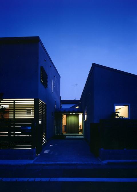 庭を挟んだ分棟型の2世帯住宅の写真 夕景