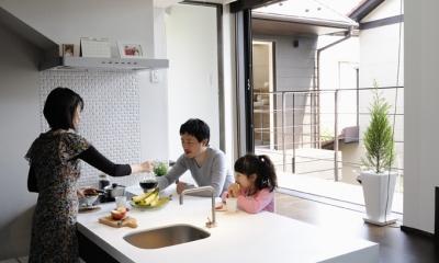 ふたつの家族と中庭の家 (子世帯のリビングから見たダイニングキッチンとバルコニー)
