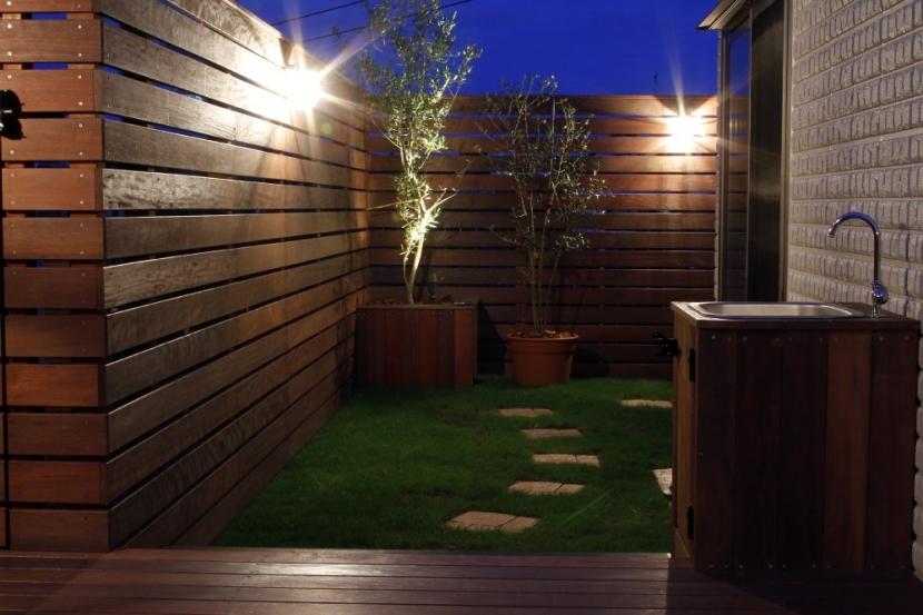 ウッドフェンスでプライバシーを確保した屋上庭園の部屋 夜はライトアップして