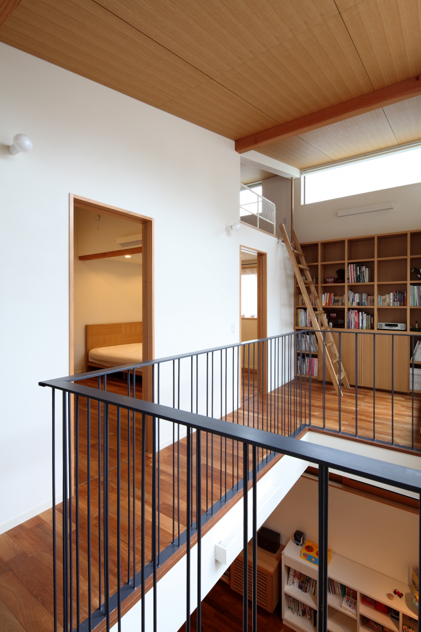 交差点に建つ光庭の家の部屋 2階吹き抜け周りのホール、子ども部屋とライブラリー