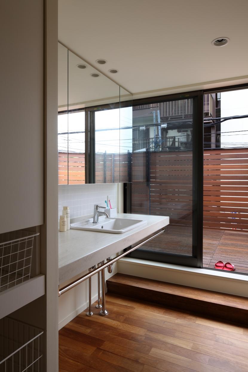 交差点に建つ光庭の家の部屋 ルーフテラスにつながるサニタリースペース