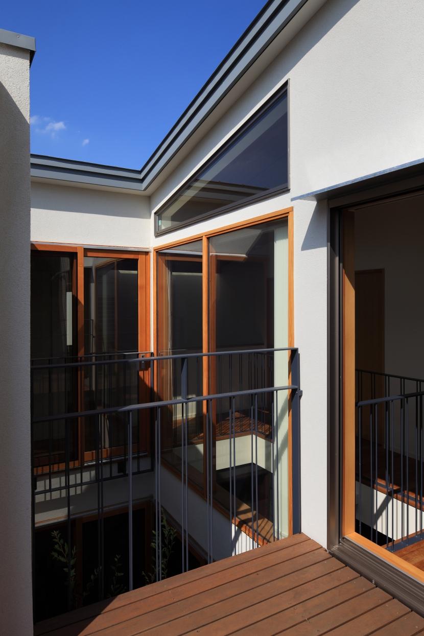 交差点に建つ光庭の家の部屋 ルーフテラスから光庭を見る