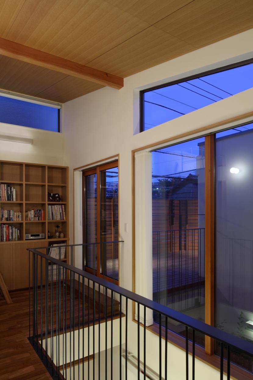 交差点に建つ光庭の家の部屋 ライブラリー越しにルーフテラスを見る