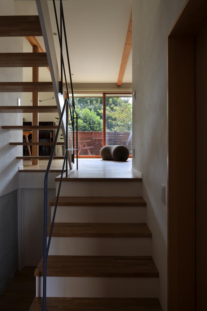 公園を借景にしたスキップフロアの家の写真 玄関からリビングへ