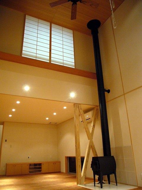 銚子の家の部屋 リビングダイニング吹抜を立上る薪ストーブの煙突