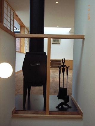 坪井町の家の部屋 階段から薪ストーブを介してリビングダイニング方向を見る