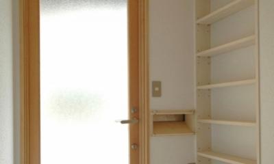 ロフトでつながる大屋根の家 (ガラスドアからの光で明るい玄関の中)