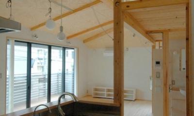 オープンなキッチンからリビングを見る|ロフトでつながる大屋根の家